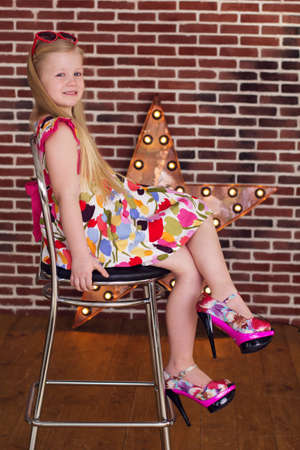 dress shoes: Beautiful little girl in dress and big mothers shoes sitting on chair over brick wall background