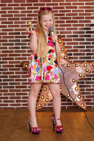 Niña hermosa en vestido de la manera y los talones de madre con el micrófono en el fondo de pared de ladrillo