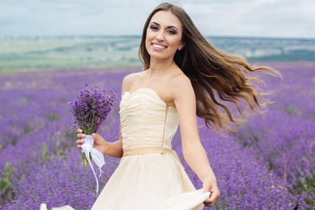 flying hair: Beautiful smiling girl at field of purple lavender flowers with flying hair Stock Photo