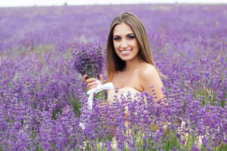 flying hair: Beautiful smiling woman is wearing wedding dress with flying hair at field of purple lavender flowers Stock Photo