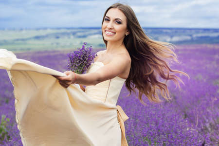 flying hair: Beautiful smiling woman with flying hair and dress holding bouquet at field of purple lavender flowers