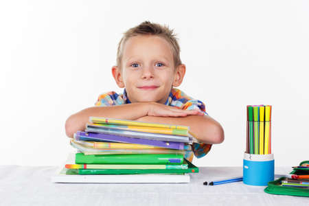smirk: Happy schoolboy with smirk is lying on like of books, isolated over white background Stock Photo