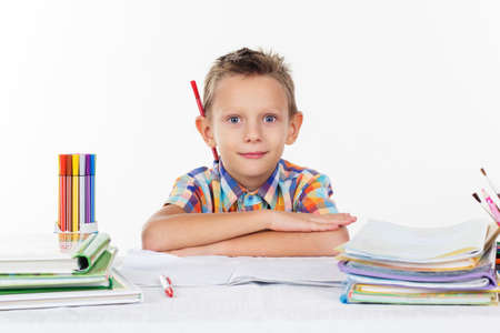 smirk: Happy schoolboy with smirk and pencil behind his ear, isolated over white background Stock Photo