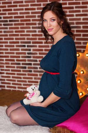 Beautiful pregnant woman is wearing dress in studio holding small teddy bear