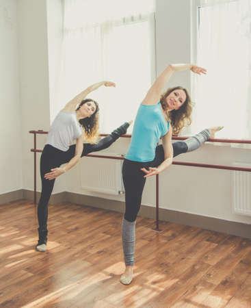 two minds: Young fit slim women are practicing ballet poses