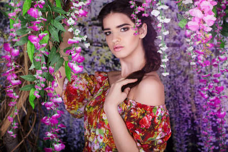 wistaria: Pretty young girl with fashion hairstyle in garden with wistaria flowers