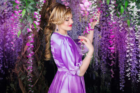 wistaria: Pretty young woman with fashion hairstyle in garden with wistaria flowers Stock Photo