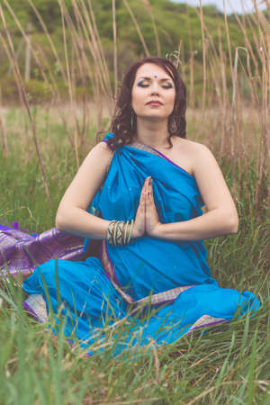 bindi: Pretty pregnant indian girl is wearing blue fashion sari dress with mehendi tattoo on hands is holding her tummy on the nature