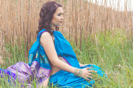 bindi: Pretty pregnant girl is wearing blue fashion indian sari dress with mehendi tattoo on hands are relaxing on the nature