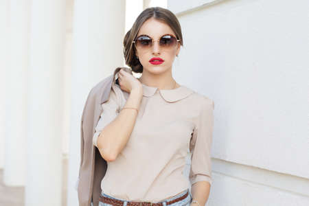 Beautiful lady is wearing sunglasses and holding jacket , business style Foto de archivo