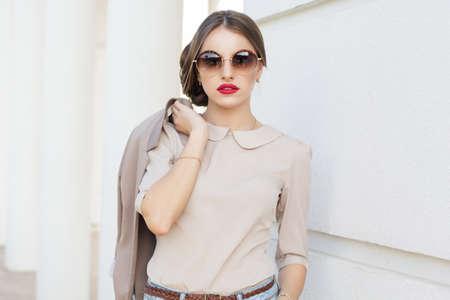 De mooie dame draagt een zonnebril en holding jasje, zakelijke stijl Stockfoto