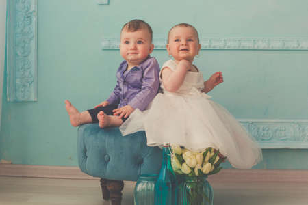 dress suit: Couple of babies boy and girl are wearing fashion clothes in studio