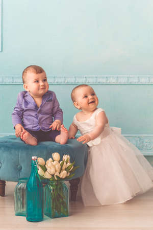Couple of babies boy and girl are wearing fashion clothes in studio