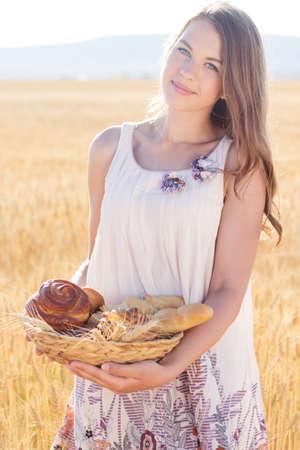 Schöne Teenager-Mädchen in einem Feld von Roggen mit Korb mit Brot und süße Brötchen zu Fuß