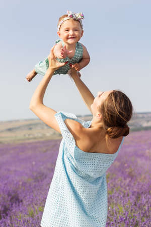 Beautiful fashion couple young mother is wearing dress having fun with her toddler daughter in purple lavender field, summer time