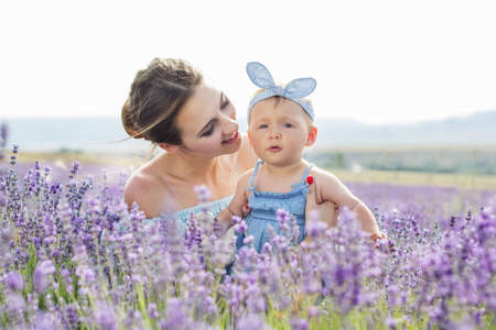 Beautiful portrait of young mother is wearing dress having fun with her toddler daughter in purple lavender field, summer time