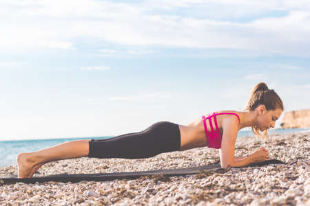 Young slim beautiful woman is wearing sportive clothes doing plank pose from yoga on mat on the beach, summer time Stockfoto