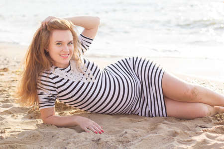 Pregnant redheared pretty girl is wearing stripped dress sitting on the sandy beach, sunset time