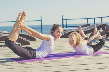 Mother and daughter doing yoga exercise on the beach