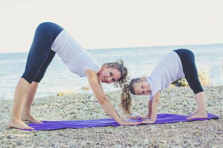 Mother and daughter are doing yoga exercise on the sea coast
