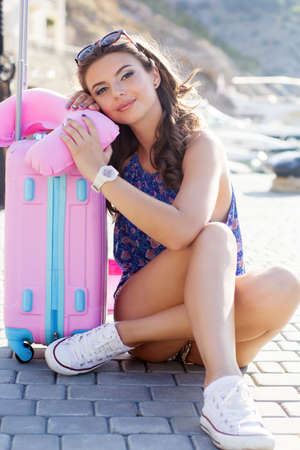 Pretty tired traveler girl is waiting for summer cruise on seafront with fashion pink bag and air cushion Stock Photo