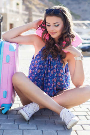 Pretty tired smiling traveler girl with pink air cushion on her neck