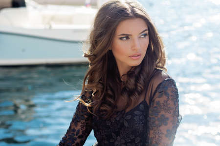 adult cruise: Portrait of pretty tanning girl is wearing fashion dress with luxury makeup sitting near sea with yachts