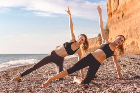 beach mat: Two young slim beautiful women are wearing sportive clothes doing pilates on mat on the beach, summer time Stock Photo