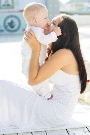 Beautiful smiling happy mom is kissing her little baby boy are wearing white fashion clothes spending time outdoors, summer time