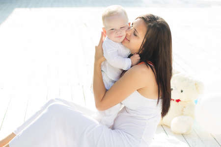 urban parenting: Beautiful smiling mom is kissing her little baby boy are wearing white fashion clothes spending time outdoors Stock Photo