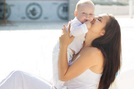 urban parenting: Beautiful smiling mom is wearing white dress is kissing her little baby boy are enjoying nice sunny day outdoors