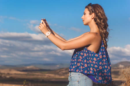 Pretty teen girl is wearing casual clothes taking picture with her phone of mountains and sky view