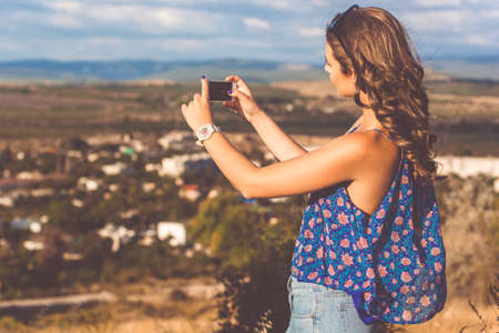Pretty teen girl is wearing casual clothes taking picture with her phone of village view