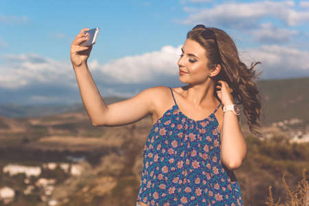 Pretty teen girl is wearing casual clothes taking selfie picture with her phone Stock Photo