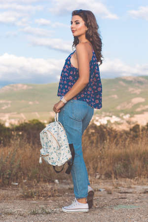 Pretty traveler teen girl is wearing casual ragged jeans standing with fashion backpack over mountains and sky background
