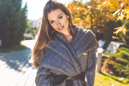 Beautiful sexy woman is wearing warm knitted gray coat in park with maple yellow leaves, autumn time
