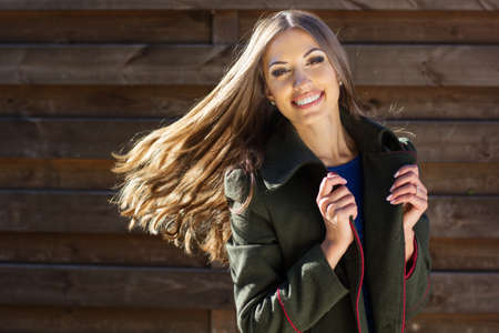 Portrait of young fashion smiling girl wearing warm coat with flying hair near wooden wall