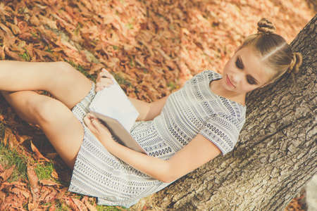 yellow notepad: Pretty sad teenager girl is in autumn park with yellow leaves with notepad
