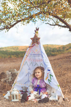 Little child girl is sitting in decorative hovel on the nature, autumn season Stock Photo