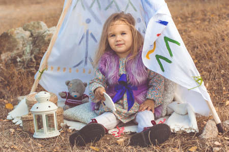 Little happy child girl is sitting in decorative hovel on the nature, autumn time Stock Photo