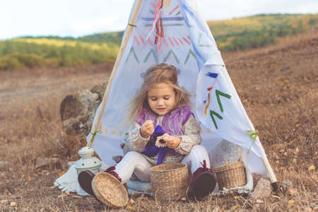 Little happy child girl is sitting in decorative hovel on the filed with mountains view Stock Photo