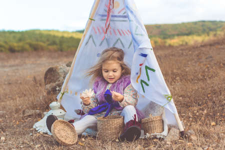 Little happy smiling child girl is sitting in decorative hovel on the filed with mountains view Stock Photo