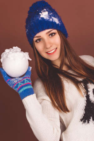 Pretty happy teenager girl is wearing white sweater and blue gloves is holding fake snowball isolated on brown background