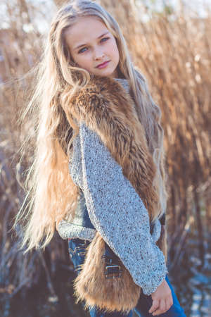 blonde teenager: Beautiful girl with long blonde hair outdoors is sitting near lake and wearing warm sweater and furry jacket Stock Photo