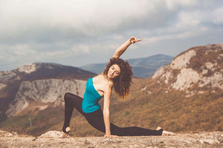 Young pretty flexible woman is doing stratching in beautiful mountains landscape view on the top of the hill