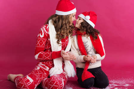 Pretty happy two sisters girls are sitting nose by nose wearing warm red winter clothes isolated on red background, christmas concept