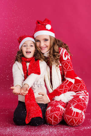 Pretty happy two sisters girls are playing with fake snow wearing warm red winter clothes isolated on red background, christmas concept Stock Photo