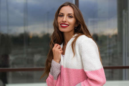 Portrait of beautiful gorgeous smiling woman is wearing handmade fashion knitted colorful cardigan posing near glass windows of office building