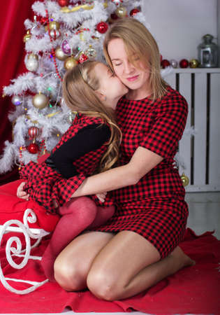 the caucasian beauty: Cute daughter is kissing her young pretty mom at home near white decorated Christmas tree