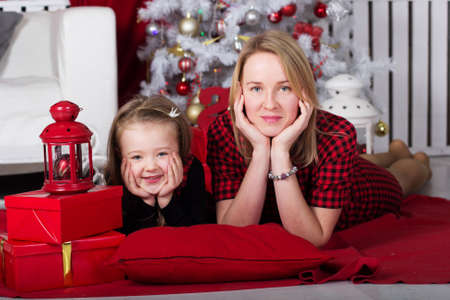 the caucasian beauty: Cute daughter with her young mother are lying on pillow at home near white Christmas tree.